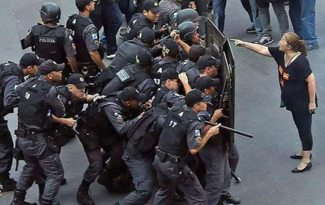Professora enfrentando cerco de policiais militares protegidos por escudos