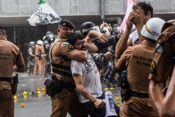 professor sendo imobilizado por policial militar durante protesto em Curitiba, 2015